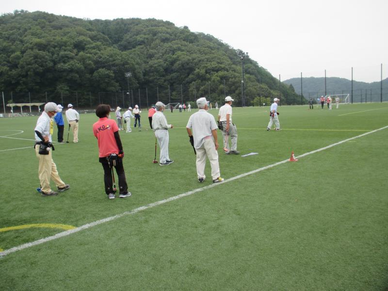 ダイセル播磨光都サッカー場の人工芝の上でグラウンド・ゴルフ競技を行う宍粟市グラウンド・ゴルフ協会の会員ら